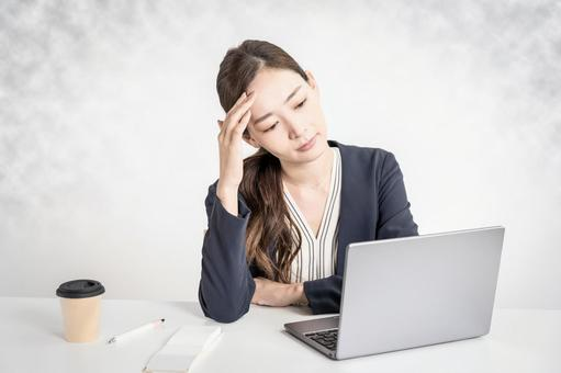 A woman holding her head in front of a computer