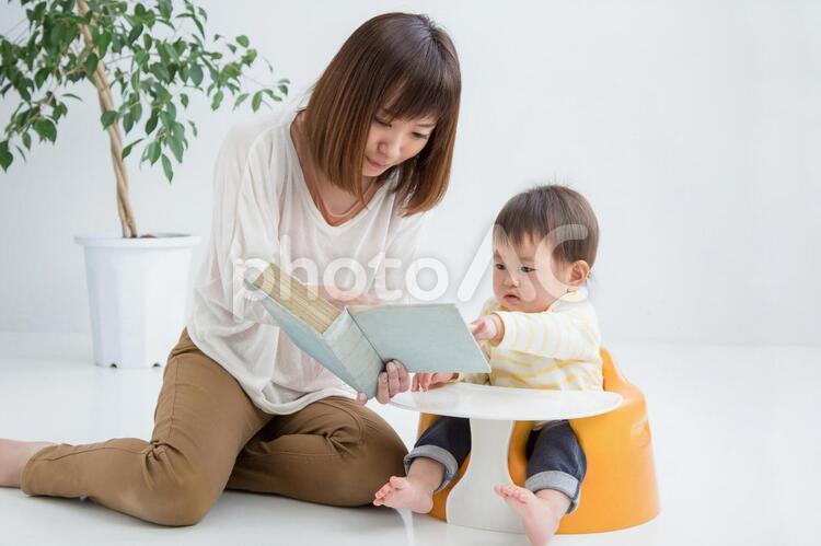 赤ちゃんに本を読む女性の写真
