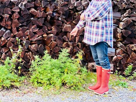 A woman wearing red boots in front of firewood