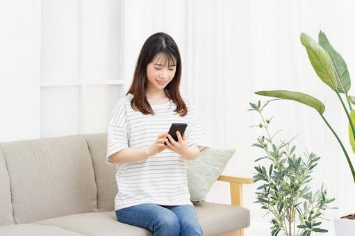 A young woman sitting on the sofa in the room and operating her smartphone