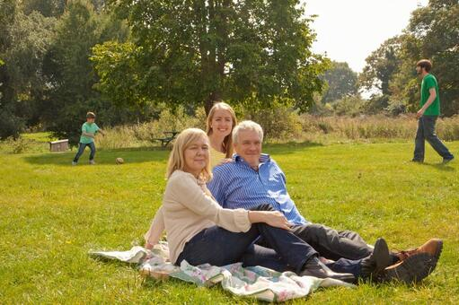 Three generation families relaxing on the lawn 4