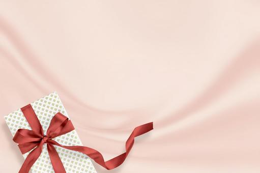 핑크 드레이프가 우아한 실크 배경에 빨간 리본 선물