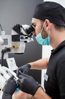Male dentist treating with microscope 16