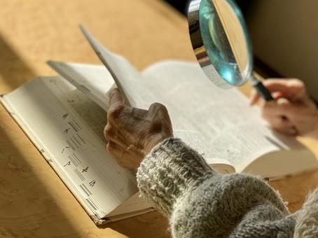 Elderly hand reading dictionary with magnifier