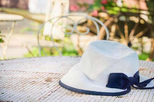 Straw hat on the table on the garden terrace / sunshade / sun protection / hat / English garden