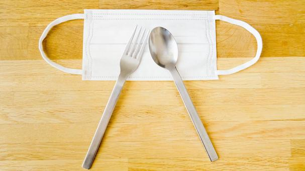 Wood grain table with mask, fork and spoon Mask Eating and drinking / silent eating image