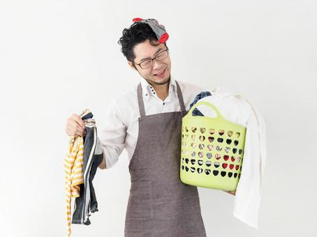 Image of a man having trouble with accumulated laundry