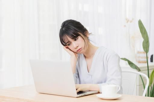 A woman worried while using a laptop in the room