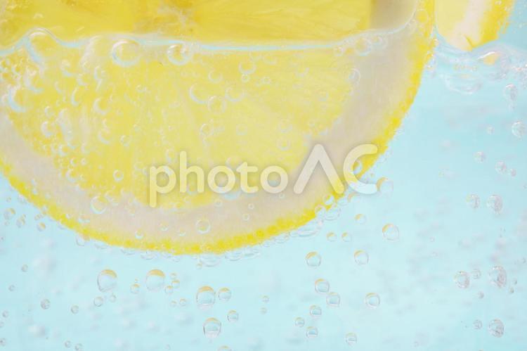 レモンと炭酸水のライトブルー背景の写真