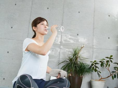 Japanese woman hydrating during training