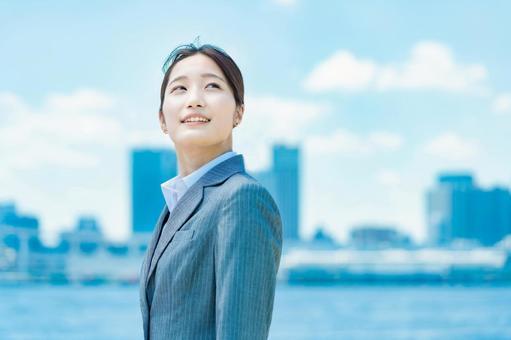一位年輕的女商人站在市中心和藍天的背景下