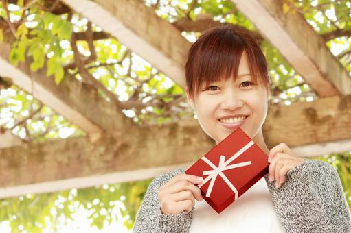 A woman with a smile with a present
