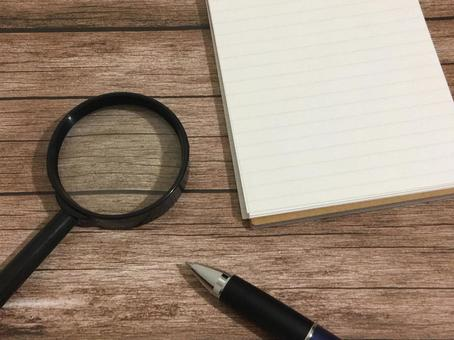 Magnifying glass, pen and notepad