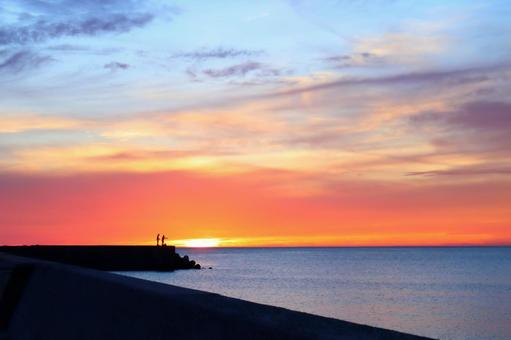 Beautiful orange and light blue sunset sky with the setting sun over the sea Angler