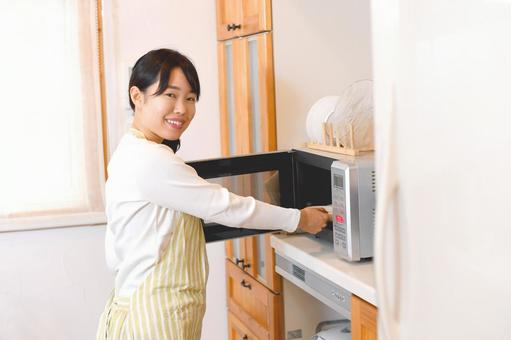 Young woman using a microwave