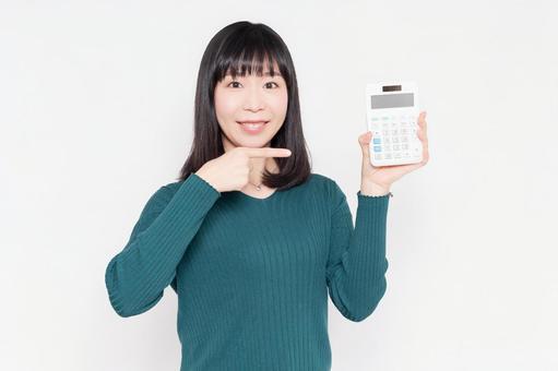 흰색 배경 앞에 서, 계산기를 보여주는 미소의 여성