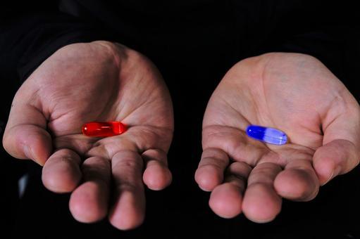 빨간색과 파란색 캡슐을 가진 남자의 손