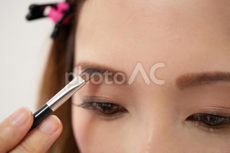 アイブロウパウダーを塗る女性の写真