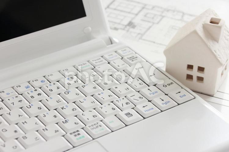 パソコンと住宅と間取り図面の写真