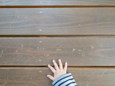 나무 벤치에 놓인 어린이의 손