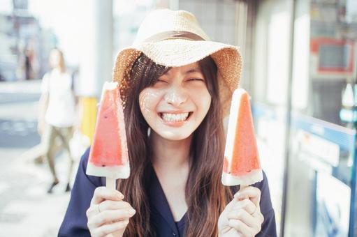 Long-haired woman in a smiling straw hat holding ice cream