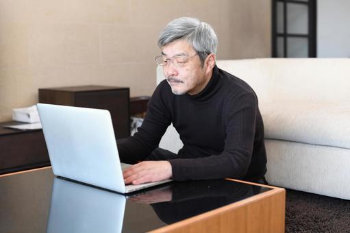Elderly (senior) gray-haired man operating a laptop