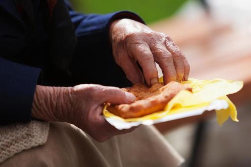 Hand of an old man grabbing food