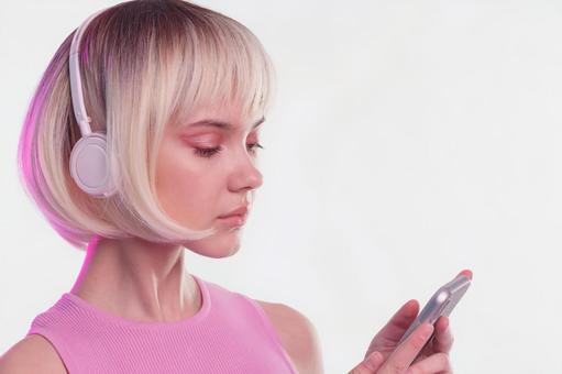 A woman wearing cyberpunk headphones and operating a smartphone