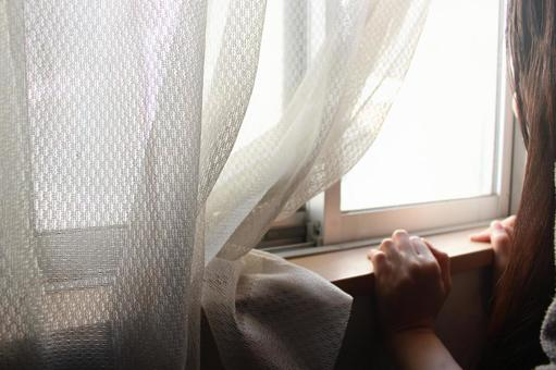 A woman looking through the window (side)
