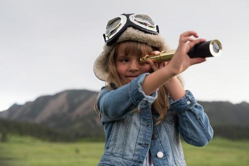 Girl looking through a telescope 1
