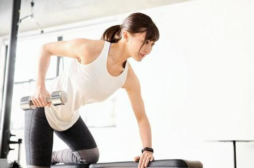 Asian woman doing one-handed rowing in a training gym