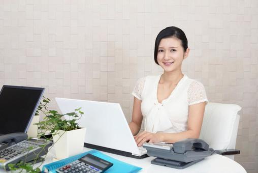 ノートパソコンで仕事中のビジネスウーマン