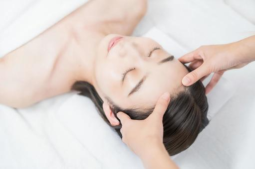 A young woman whose head is massaged at an esthetic salon