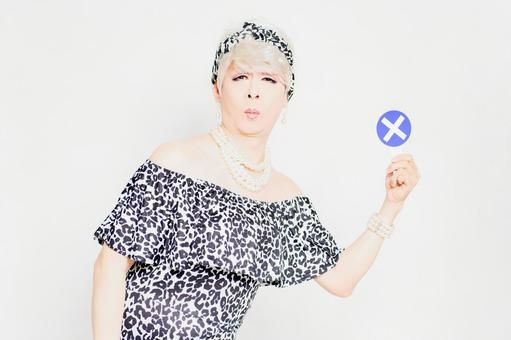 Drag queen with NG placard standing in front of white background