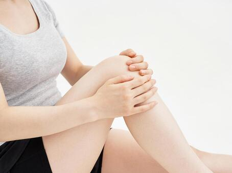 A woman holding a painful knee on a white background
