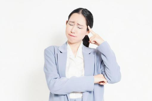 A woman standing in front of a white background and posing to think
