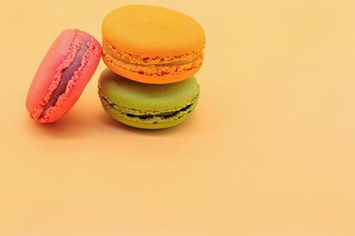 Three macaroons lined up with a beige background