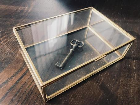Key up in a glass case on the desk