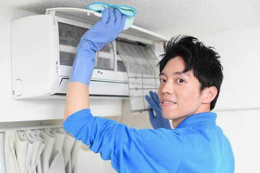 Young man in work clothes cleaning the air conditioner