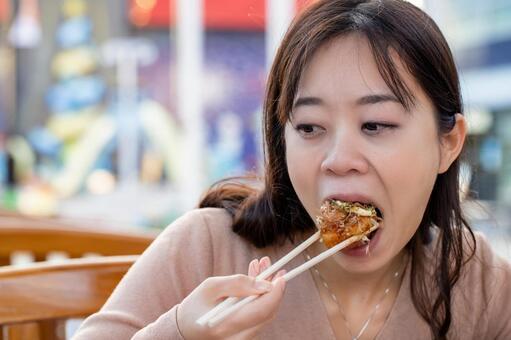 在露台上吃章魚燒的女性肖像