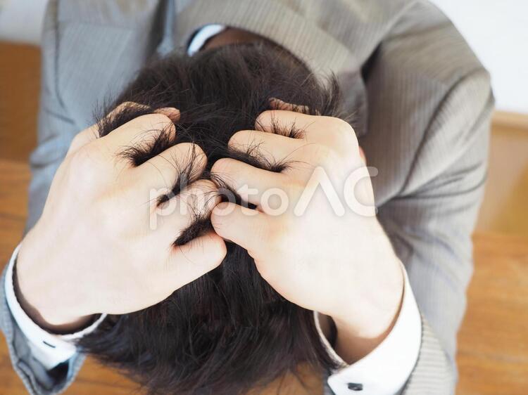 ビジネスマン【頭を抱える男性】の写真