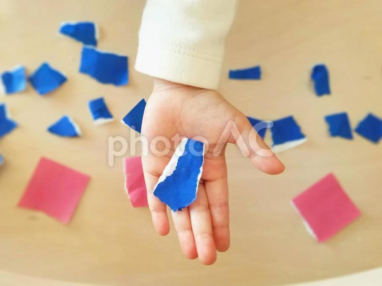 折り紙をちぎる子どもの手の写真