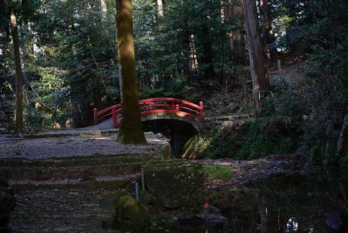 A vermilion bridge over a stream in the forest