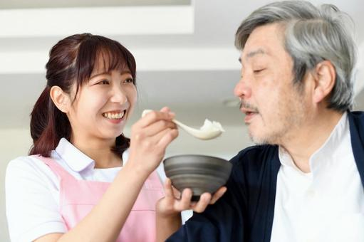 A young woman in an apron helping a senior man eat