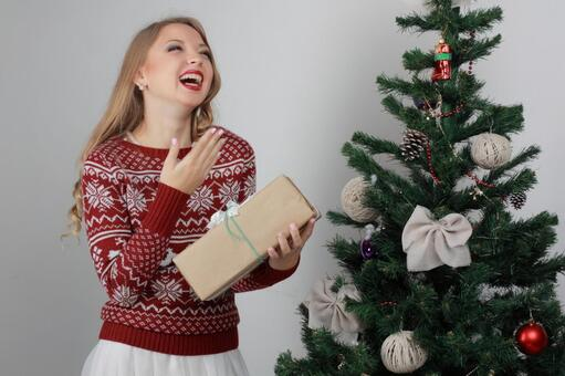 A woman with a Christmas tree and a present 10