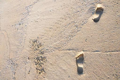 Footsteps of bare feet on the beautiful sandy beach of Okinawa white sand