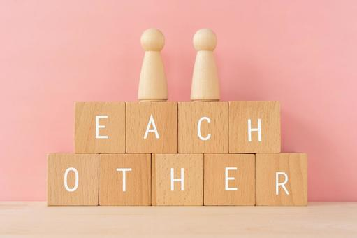 """Helping each other, both sides   Building blocks and humanoid objects with """"EACH OTHER"""" written on them"""