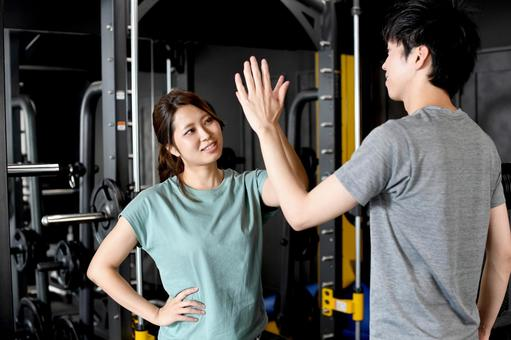Men and women in high five doing pair training in the gym