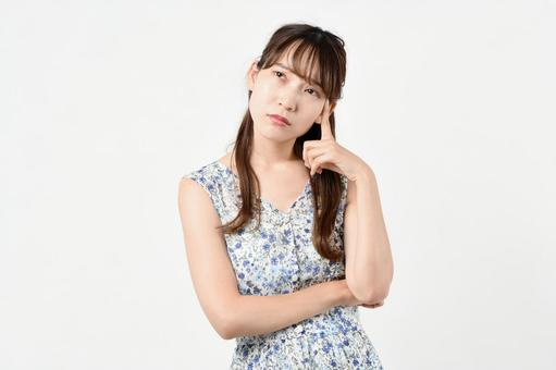 A young woman in plain clothes worried in front of a white background