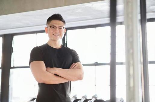 Asian male trainer with a smile and arms folded
